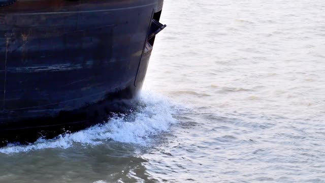 close up of the ship's prow sailing in river. the nose of the cargo ship cuts the water creating small waves on the water. super slow motion. - natante industriale video stock e b–roll