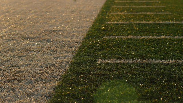 Close up of the turf on a football field, pan up with lens flare video