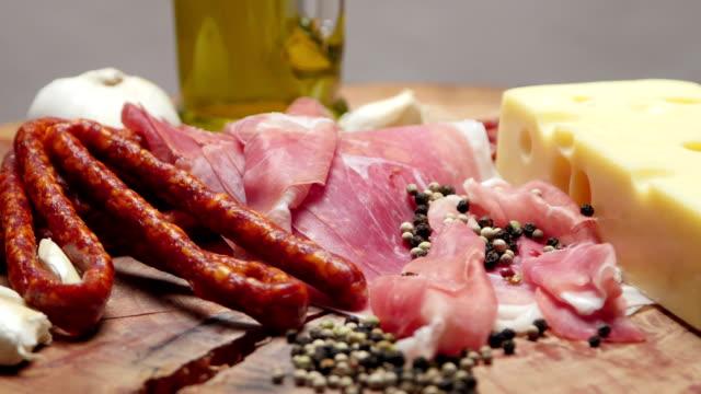 vídeos de stock, filmes e b-roll de close-up de fatias finas de presunto com secas crus salsichas e queijo suíço na tábua de madeira - salsicha