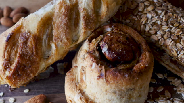 Close up of three delicious pastries on a beautiful cutting board Close up of three delicious pastries on a beautiful cutting board including a cinnamon bun, and oatmeal jam roll bun bread stock videos & royalty-free footage