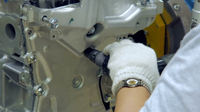 close up of tightening bolts in car engine, by worker, hands with gloves, special tool
