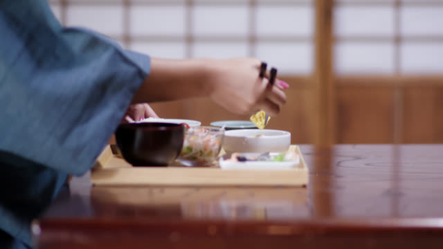 nahe von touristen in einem ryokan essen ein traditionelles japanisches mittagessen - japanisches essen stock-videos und b-roll-filmmaterial