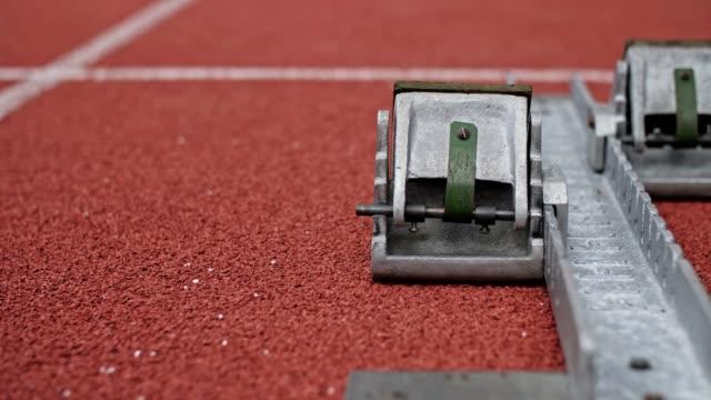 vidéos et rushes de fermez-vous vers le haut du bloc de commencement de voie au champ d'athlétisme. - starting block