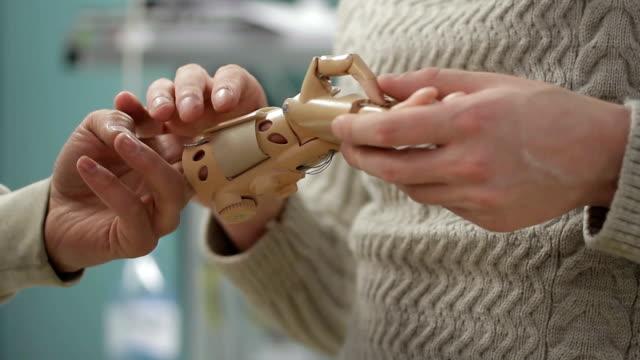 人工の手の肢を議論する 2 つのエンジニアのクローズ アップ - 四肢点の映像素材/bロール