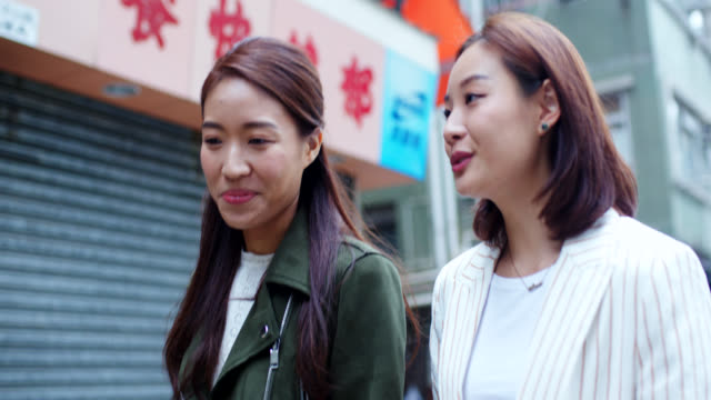 close up of two friends walking through the city - cultura orientale video stock e b–roll