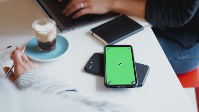 Close Up Of Two Green Screen Mobiles Phone To Phone Wirelessly Charging On Desk