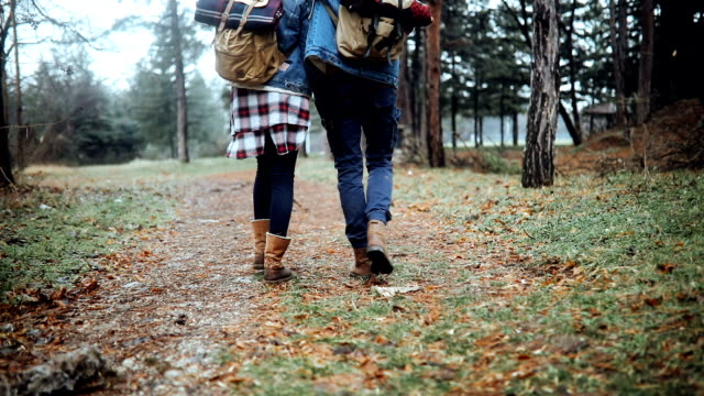 Close up of two hikers walking embraced in forest video