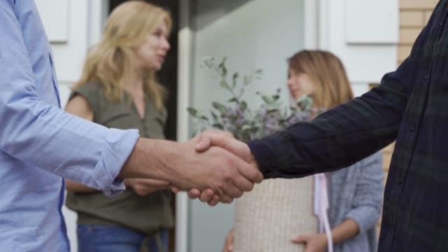 stockvideo's en b-roll-footage met close-up van twee mannen schudden handen op de voorgrond terwijl hun vrouwen chatten op de achtergrond - buren