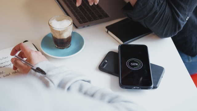 Close Up Of Two Mobiles Phone To Phone Wirelessly Charging On Desk