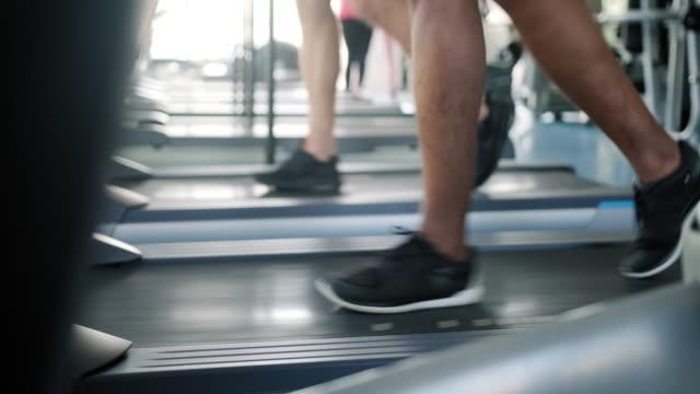 vídeos de stock e filmes b-roll de close up of two people running on treadmill - aparelho de musculação