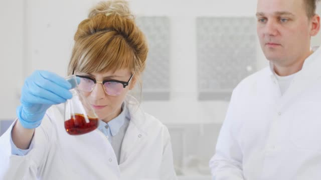 Close up of two scientists working with CBD oil Close up of chemical scientists working with hemp CBD and CBDa oil in laboratory. They are using erlenmeyer flasks. Cannabis pharmaceutical healthcare concept. cbd oil stock videos & royalty-free footage