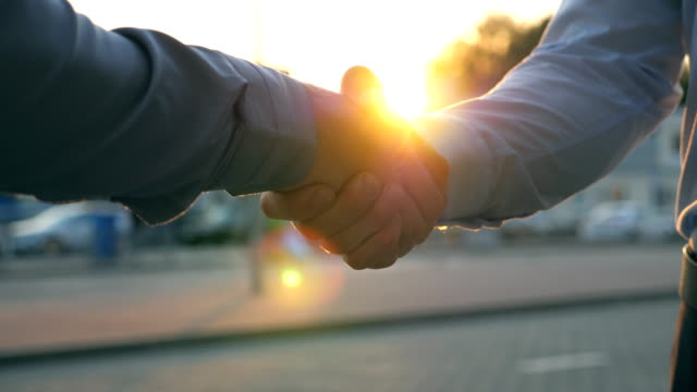 close up of two successful businessmen greeting each other against the background of cars parking. young colleagues meeting and shaking hands at city street on sunset. business handshake outdoor. - fiducia video stock e b–roll