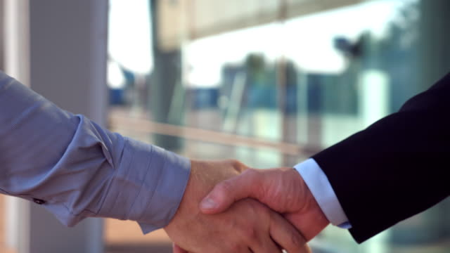 Close up of two successful businessmen greeting each other in urban environment. Young colleagues meeting and shaking hands near office building. Handshake of business partners outdoor. Side view