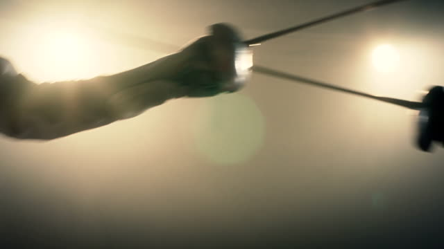 vídeos de stock e filmes b-roll de close up of two swords and fencing athletes duel . two professional fencers show masterful swordsmanship in their foil fight. shot on arri alexa cinema camera in slow motion . - cercado
