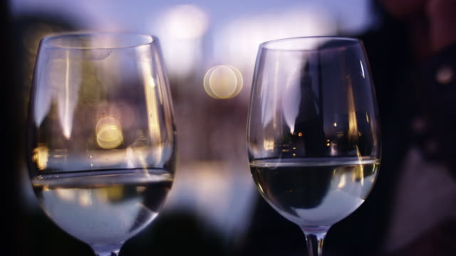 Close up of two wine glasses being toasted at dusk video