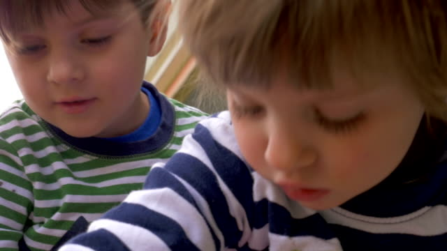 Close up of two young children a boy and girl focused on playing together video