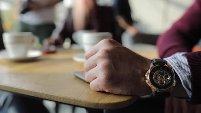 vídeos de stock e filmes b-roll de close up of unrecognizable businessman with wristwatch - coffee table
