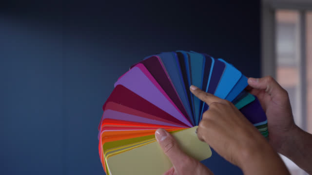 Close up of unrecognizable couple pointing at different colors on a color swatch at their new home