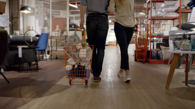 Close up of unrecognizable couple shopping at a furniture store and pulling a cart with products