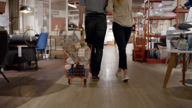 stockvideo's en b-roll-footage met sluit omhoog van onherkenbaar paar dat bij een meubilairopslag winkelt en een kar met producten trekt - decoraties