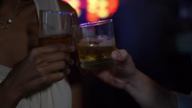バーでウイスキーで乾杯する認識できないカップルのクローズアップ - バーカウンター点の映像素材/bロール