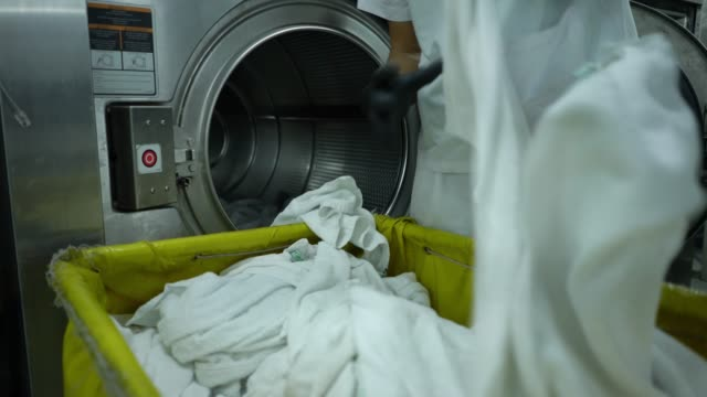 Video Close up of unrecognizable employee loading washing machine with white towels