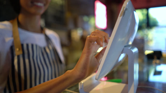 Close up of unrecognizable female waitress registering an order on system Close up of unrecognizable female waitress registering an order on system at a coffee shop wait staff stock videos & royalty-free footage