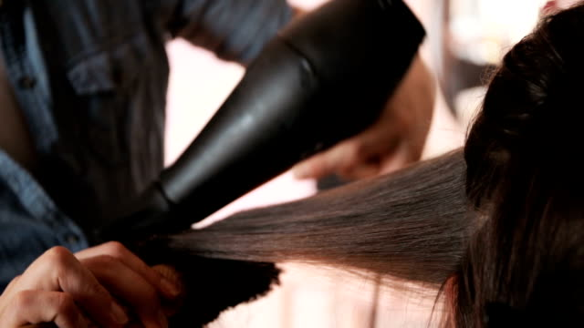 Close up of unrecognizable hairdresser using hair dryer and round brush while drying customers hair. video