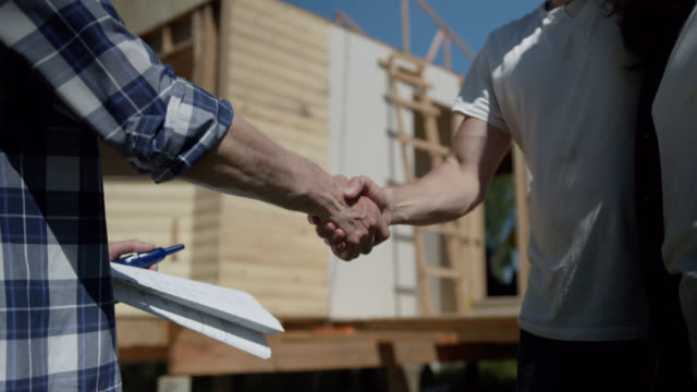 close up of unrecognizable man and his partner handshaking building contractor at their new home project - imprenditore edile video stock e b–roll