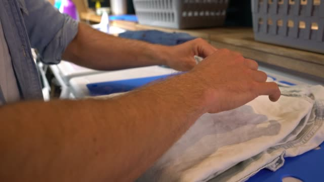 Close up of unrecognizable man folding his shirts at a laundromat