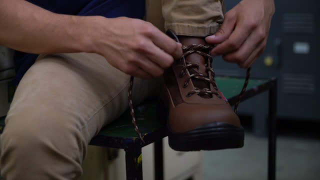 vídeos de stock e filmes b-roll de close up of unrecognizable man putting on his working boots and trying them - bota
