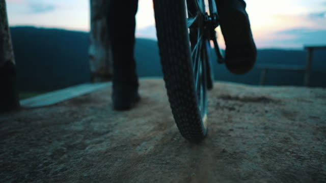 Close up  of unrecognizable  man spinning back wheel of his mountain bicycle on dirt ground. video