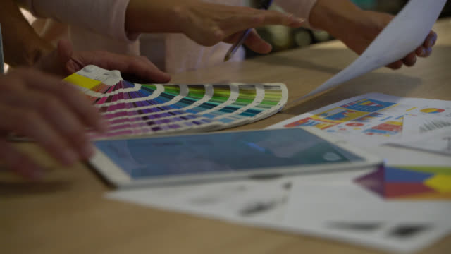 close up of unrecognizable people looking at a blueprint on tablet and a color swatch - tavolozza video stock e b–roll