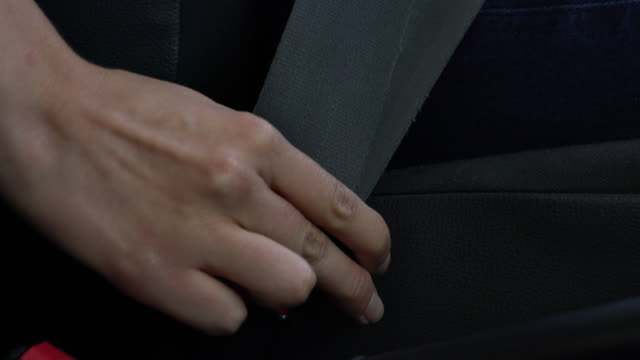 Close up of unrecognizable person buckling the seat belt