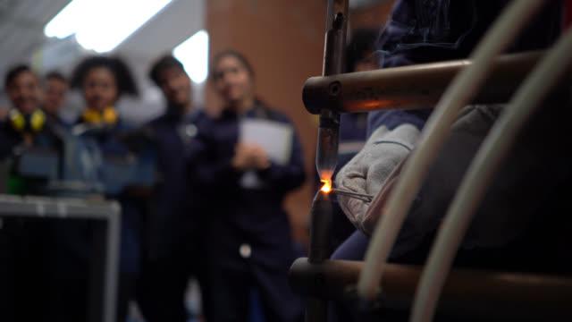 vídeos de stock, filmes e b-roll de feche de professor irreconhecível mostrando aos seus alunos como soldar pedaços de arame grosso juntos durante a aula de oficina - soldar