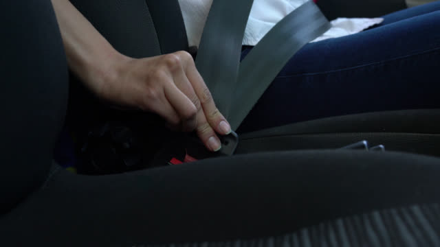 Close up of unrecognizable woman buckling her seat belt video