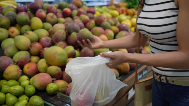 Close up of unrecognizable woman choosing fruits from retail display and adding them to a plastic bag Close up of unrecognizable woman choosing fruits from retail display and adding them to a plastic bag - Lifestyles mango stock videos & royalty-free footage