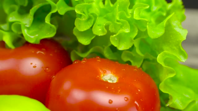 Close - up of vegetables on a plate. Concept of healthy food and organic food. Tomatoes, lettuce leaves, a woman's hand takes the lettuce and shakes off drops of water. In slow motion.