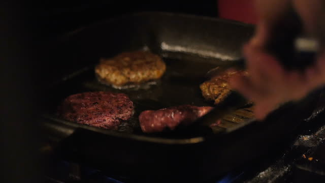 close up of vegetarian burger grilling on a griddle pan. healthy food. - vegan stock videos and b-roll footage