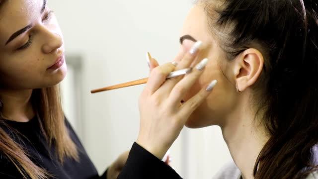 Close up of visagist doing makeup, coloring eyebrows with mascara video