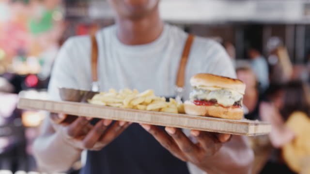 Close up of waiter holding tray of burger and fries in busy bar restaurant and bringing them into focus in front of camera - shot in slow motion Close Up Of Waiter Serving Burger And Fries In Busy Bar Restaurant¾ wait staff stock videos & royalty-free footage