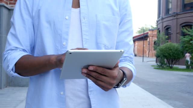 Close Up of Walking Man and Using Tablet for Browsing video