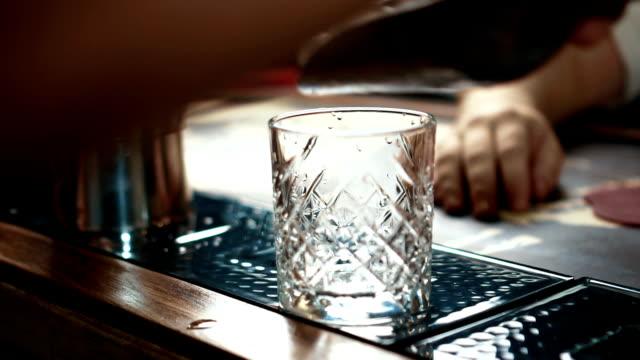 nahaufnahme von whiskyglas mit eis in stilvollen bar, slow-motion erfüllt - turngerät mit holm stock-videos und b-roll-filmmaterial