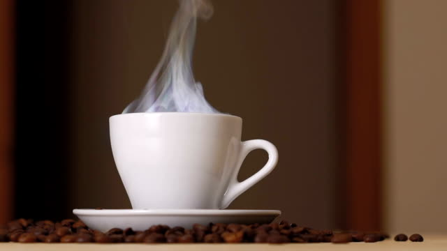 nahaufnahme des weißen tasse verdampfenden kaffee am tisch in der nähe von gerösteten bohnen. langsam - kaffeetasse stock-videos und b-roll-filmmaterial
