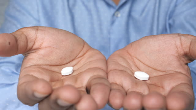 close up of white pills on palm of hand - antidolorifico video stock e b–roll