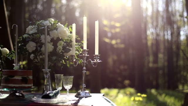 vídeos de stock, filmes e b-roll de perto de um branco vintage candelabro sobre a mesa decorada para casamento na floresta. buquê de rosas brancas sobre fundo. jantar romântico na floresta - rústico