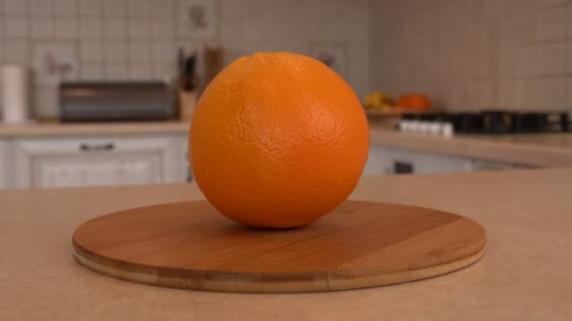 close up of whole orange fruit. rotating camera with white kitchen on the background. dolly-shot. - desserts stock videos and b-roll footage