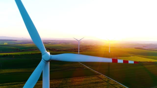 närbild av vindkraft generatorer vid solnedgången. - vindsnurra jordbruksbyggnad bildbanksvideor och videomaterial från bakom kulisserna