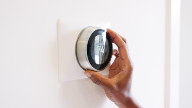 ana sayfa-shot ağır çekimde, akıllı termostat ayarlama kadının yakın çekim - ayarlamak stok videoları ve detay görüntü çekimi