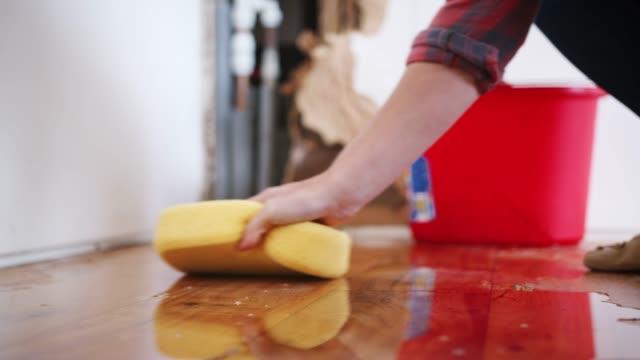パイプの漏れから水をホーム掃討で女性のクローズ アップ - ダメージ点の映像素材/bロール
